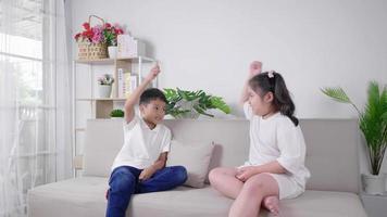2 crianças sentadas e jogando pedra, papel tesoura, junto com uma cara feliz e rindo no sofá na sala de estar em casa, irmã e irmão conceito de atividades divertidas video