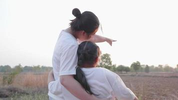 Back wide view of Asian mother point out and tell to daughter to looking far at field forest landscape then girl looking too and point fingers follow mom Mom and kid close hug and talk together video
