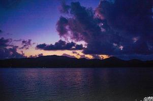 puesta de sol púrpura sobre el agua foto
