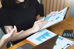 Focus on hand holding pen that points to chart document photo