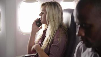 Young woman using mobile phone on airplane flight video