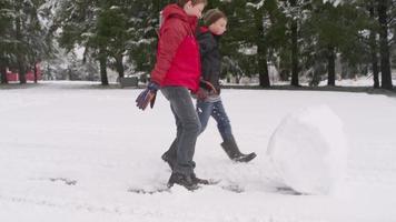 dois meninos rolando uma bola de neve no inverno video