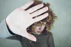 Primer plano de la palma de la mano de una mujer joven y hermosa que cubre su rostro, su cabello es rizado y rubio, se ve enojada o cansada foto