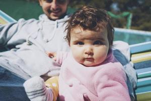 pequeño bebé disfrutando de un día soleado en vacaciones con papá foto