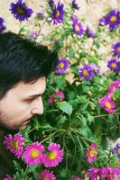 Closeup side view of a young attractive man in calm looking and smelling outdoor flowers photo