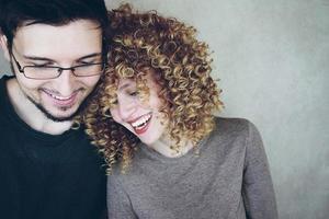 Retrato de una pareja caucásica natural de mujer joven con cabello rubio rizado y un hombre que comparten tiempo juntos y sonríen mientras se divierten foto