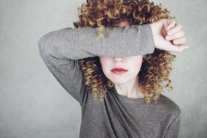 Primer plano de una hermosa y joven mujer con cabello rubio rizado cubre su rostro con su brazo, parece enojada o cansada foto