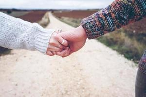 Primer plano de una joven pareja tomados de la mano mostrando su compromiso en un viaje de aventura en un camino rural al aire libre como profundidad de campo foto