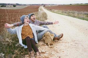 Pareja de jóvenes millennials abrazándose y gritando por una mochila en un viaje de aventura en un camino campestre al aire libre foto