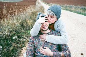 Pareja de jóvenes millennials abrazándose y sonriendo en un viaje de aventura en un camino campestre al aire libre foto
