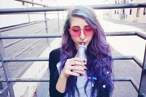 Feliz hermosa adolescente con gafas de sol rosa bebe y disfruta de una bebida rosa sentada en suelo urbano foto