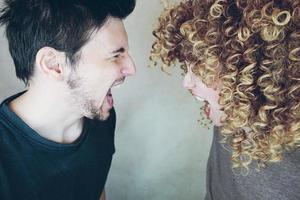 retrato, de, un, natural, caucásico, pareja, de, mujer joven, con, rizado, pelo rubio, y, hombre, de lado, gritar, y, discutir, uno al otro foto
