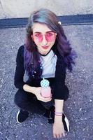 Happy beautiful teen with pink sunglasses drinks and enjoys a pink beverage sitting on urban ground photo