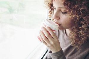 Closeup retrato de una bella y joven mujer con ojos azules y cabello rubio rizado bebe café o té mientras está en un viaje foto