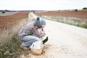 Pareja de jóvenes millennials abrazándose y descansando junto a una mochila en un viaje de aventura en un camino rural al aire libre foto