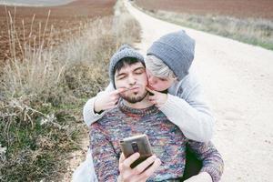 Pareja de jóvenes millennials divirtiéndose y bromeando con expresión divertida frente a un teléfono inteligente en un viaje de aventura en un camino rural al aire libre foto