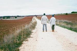 Pareja de jóvenes millennials de pie y tomados de la mano contemplando el horizonte en un viaje de aventura en un camino rural al aire libre foto