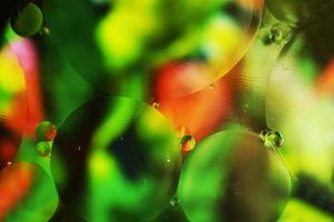 A beautiful and colorful macro of oil bubbles on water with a green, red and black floral texture as background pattern with a vintage filter photo