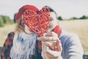 Precioso primer plano de un hermoso corazón rojo sostenido por una joven pareja romántica enamorada en un bonito bokeh como fondo al aire libre. recuerda el amor o el cuidado de la salud foto