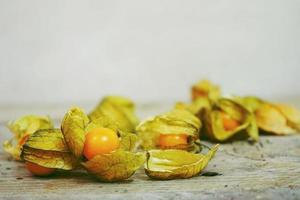 Beautiful and elegant macro close-up of a lot orange tasty fruit named physalis from Peru, South America, over wooden tables photo