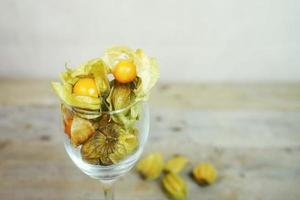 Beautiful and elegant macro close-up of a lot orange tasty fruit named physalis from Peru, South America, in a crystal glass with space over wooden tables photo