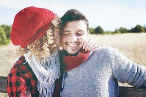 Romántica pareja joven de una hermosa mujer rubia con el pelo rizado y con un gorro de lana roja besando a su novio y un hombre guapo al aire libre foto