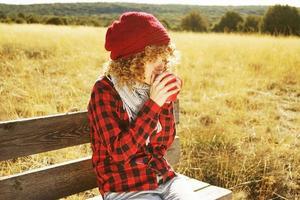 Retrato frontal de una mujer joven con camisa a cuadros roja con gorro de lana y bufanda tomando una taza de té o café mientras toma el sol sentada en un banco de madera en un campo amarillo con luz de fondo del sol otoñal foto