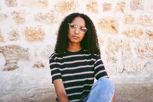 Un retrato de mujer negra joven seria con gafas, jeans y una camiseta a rayas, sentada en el suelo y cabello rizado foto