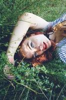 Joven y bella mujer pelirroja posando rodeada de naturaleza foto