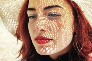 mujer joven pelirroja que cubre del sol foto