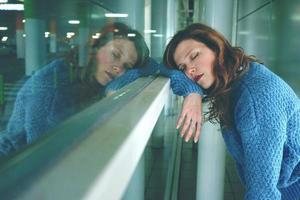 mujer joven sola y cansada en una estación de autobuses foto