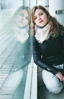 Mujer hermosa joven reflejada en una ventana enorme foto