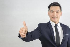 Handsome businessman Thumb up on gray photo