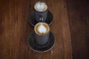 Arte latte caliente con vidrio negro sobre mesa de madera foto