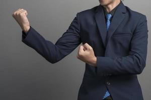 Close up of businessman in blue suit Fighting on gray background photo