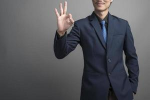Close up of businessman in blue suit hand ok on gray background photo