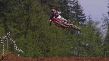 Motocross racers going over big jump in slow motion 4K fully released video