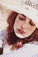 Redhead model protecting herself from sun with a hat in summer photo