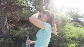 A young woman runner drinking water during her workout video
