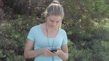 A young woman runner putting on earbuds before going on a run. video