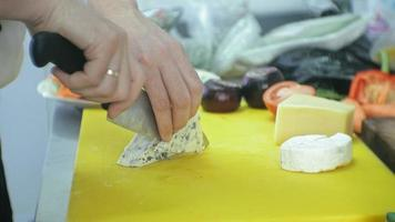 Chef slices cheese in the kitchen of the restaurant video