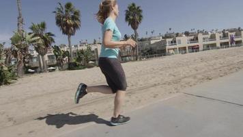 en kvinnalöpare som springer på stranden. video