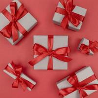 Gift boxes wrapped in craft paper with red ribbons and bows. Festive monochrome flat lay. photo