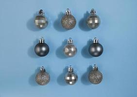 Metallic color Christmas balls on a blue pastel paper. Festive symmetry flat lay. photo
