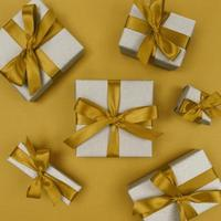Gift boxes wrapped in craft paper with yellow ribbons and bows. Festive monochrome flat lay. photo