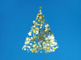 Christmas tree shape from golden confetti stars on a blue paper. photo