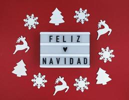 Light box with Feliz Navidad phrase, Spanish Merry Christmas on a red background with wooden toys. photo