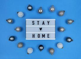 Light box with stay home quote on a blue background with Christmas balls. photo