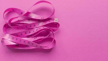 Pink centimeter on pink background. Simple flat lay with pastel texture. Fitness concept. Stock photo. photo