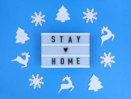 Light box with Stay home quote on a blue background with christmas toys. photo